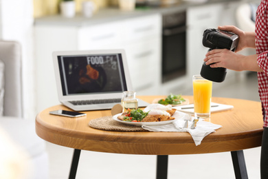 Food blogger taking photo of her lunch at wooden table indoors, closeup