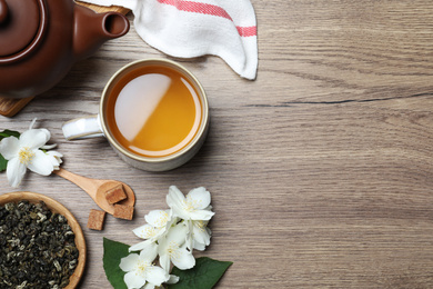 Flat lay composition with tea and fresh jasmine flowers on wooden table. Space for text