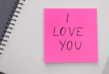Memory sticker with phrase I Love You on notebook, top view. Valentine's Day celebration
