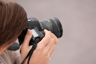 Male photographer with professional camera on grey background. Space for text