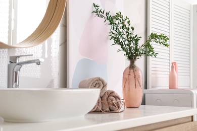 Vase with beautiful branches and fresh towels near vessel sink in bathroom. Interior design