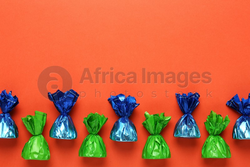 Many candies in colorful wrappers on orange background, flat lay. Space for text