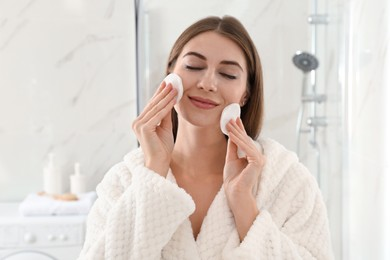 Young woman with cotton pads cleaning her face in bathroom