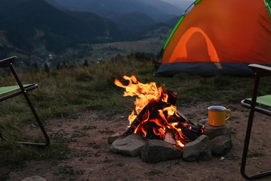 Metal mug with drink and beautiful bonfire near camping tent in mountains