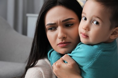 Depressed single mother with child at home, closeup