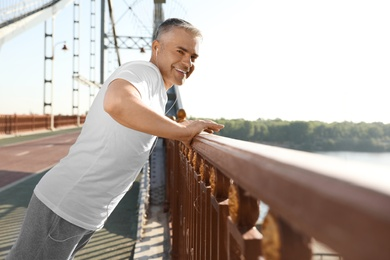 Handsome mature man in sportswear doing exercise on bridge. Healthy lifestyle