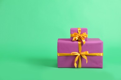 Beautifully wrapped gift boxes on green background. Space for text