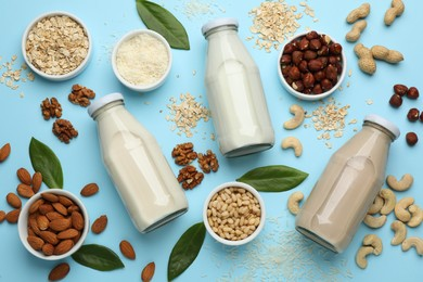 Different vegan milks and ingredients on light blue background, flat lay