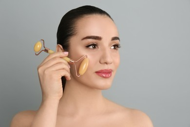 Woman using natural jade face roller on grey background