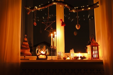 Burning candles and Christmas decor on window sill at night
