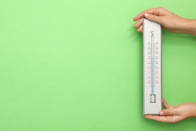 Woman with weather thermometer on green background, closeup. Space for text