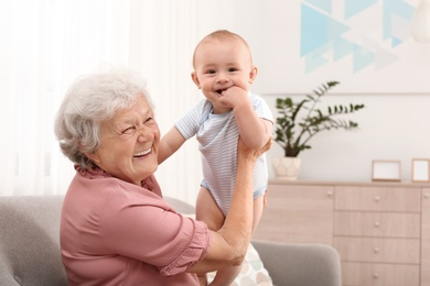 Happy grandmother with little baby at home