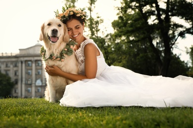 Bride and adorable Golden Retriever wearing wreath made of beautiful flowers on green grass outdoors