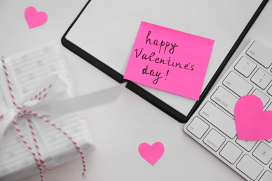 Memory sticker with phrase Happy Valentine's Day on clipboard at table, flat lay