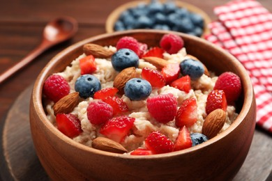 Tasty oatmeal porridge with berries and almond nuts in bowl served on table, closeup