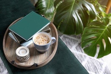Wooden tray with books, coffee and candle on bench indoors