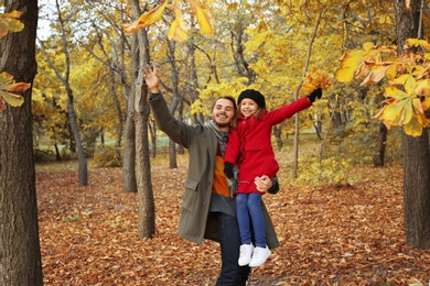 Father and his cute daughter spending time together in park. Autumn walk