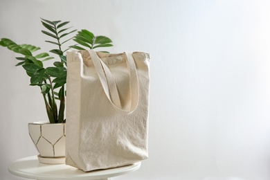Houseplant and eco bag on table near white wall. Space for text