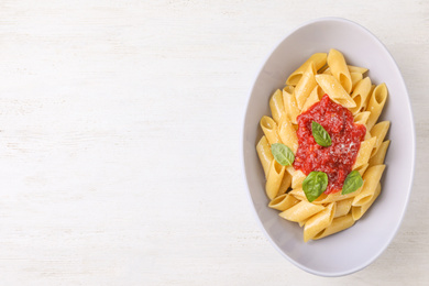 Tasty pasta with tomato sauce, basil and cheese on white wooden table, top view. Space for text
