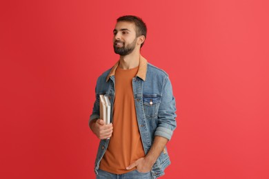 Happy student with books on red background