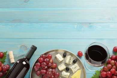 Tasty red wine and snacks on light blue wooden table, flat lay. Space for text