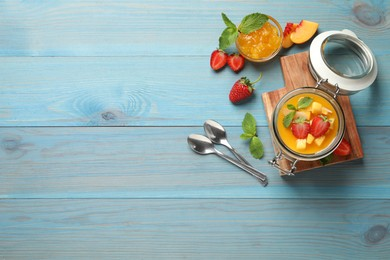 Delicious mango jelly with fresh fruits on light blue wooden table, flat lay. Space for text
