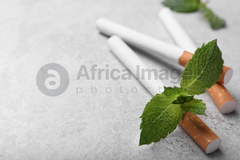 Menthol cigarettes and mint leaves on grey table, closeup. Space for text