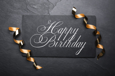 Slate board with greeting HAPPY BIRTHDAY and serpentine streamers on black background, top view