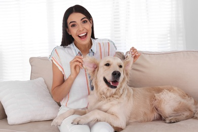 Young woman and her Golden Retriever dog having fun on couch in living room