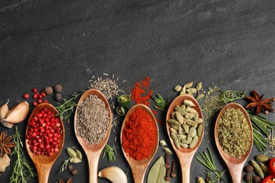 Flat lay composition with different natural spices and herbs on black table, space for text