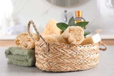 Natural loofah sponges in wicker basket and towel on table indoors