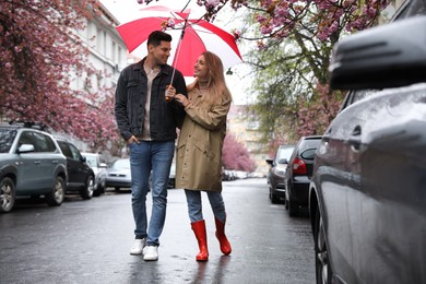 Lovely couple with umbrella walking on spring day