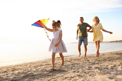 Happy parents with their child playing with kite on beach. Spending time in nature