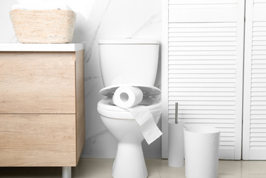 New paper roll on toilet seat in bathroom