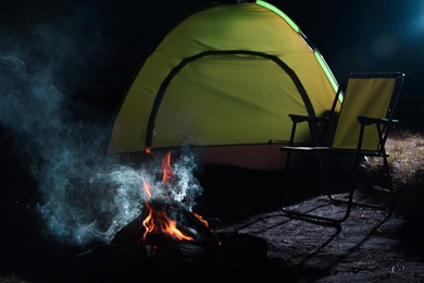 Beautiful bonfire and folding chair near camping tent outdoors at night