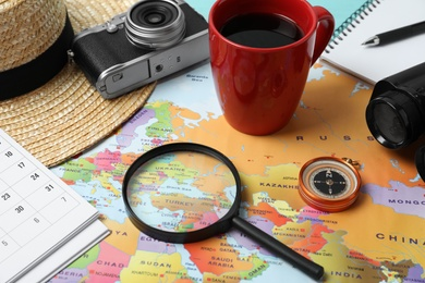 Different travel accessories on world map, closeup. Planning summer vacation trip