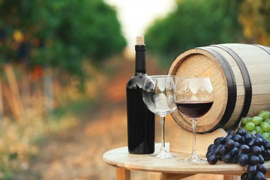 Bottle of wine, barrel and glasses on wooden table in vineyard