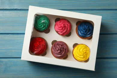 Box with different cupcakes on light blue wooden table, top view