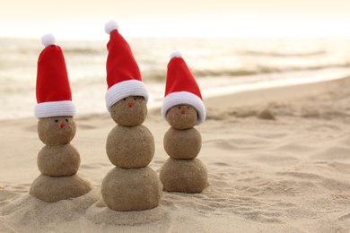 Snowmen made of sand with Santa hats on beach near sea, space for text. Christmas vacation