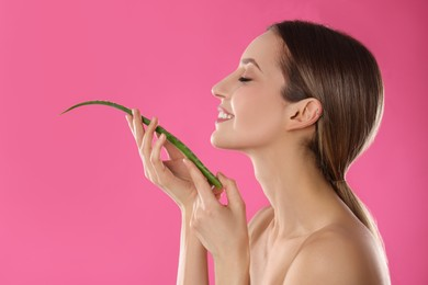 Young woman with aloe leaf on pink background