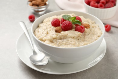 Tasty oatmeal porridge with raspberries and almond nuts served on light table