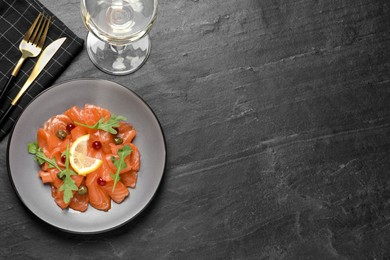 Salmon carpaccio with capers, cranberries, arugula and lemon served on black table, flat lay. Space for text