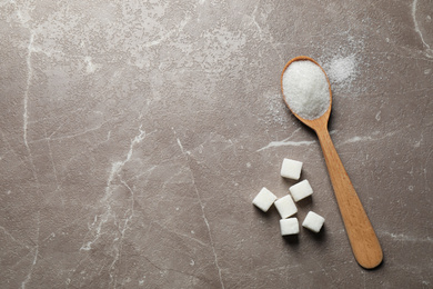 Spoon of white sugar on marble table, flat lay. Space for text