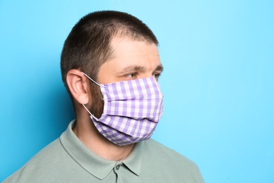 Man wearing handmade cloth mask on light blue background, space for text. Personal protective equipment during COVID-19 pandemic