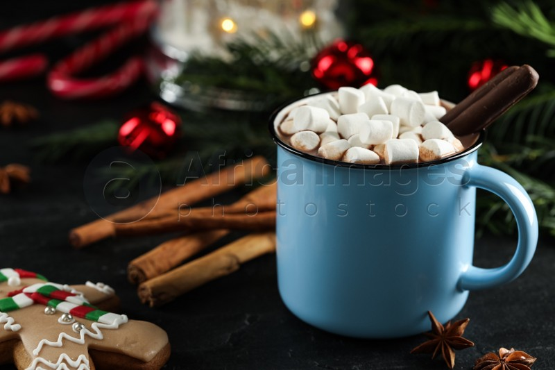 Delicious hot chocolate with marshmallows and cocoa sticks near Christmas decor on black table, closeup. Space for text