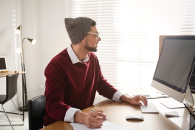 Freelancer working on computer at table indoors
