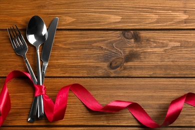 Cutlery set and red ribbon on wooden background, flat lay with space for text. Valentine's Day dinner