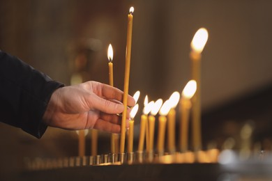 Man putting candle on stand in church, closeup. Baptism ceremony