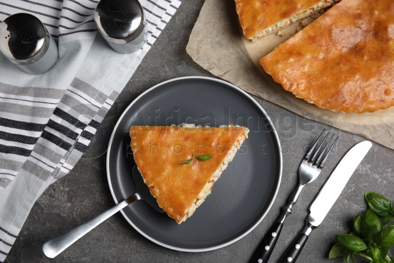 Delicious pie with meat and basil on grey table, flat lay