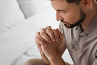 Religious man praying in bedroom, closeup. Space for text